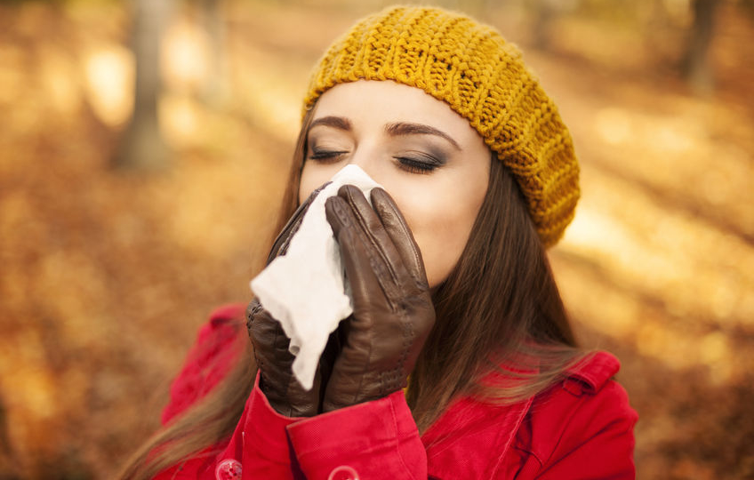 23260660 - woman sneezing in handkerchief at autumn